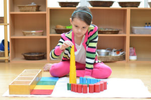 Girl building Montessori tower